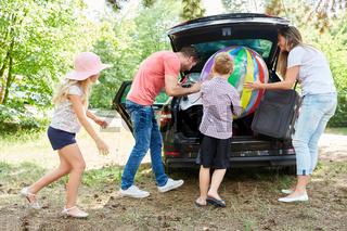 Familie und Kinder beladen das Auto