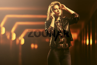Young fashion blond woman in leather jacket talking on cell phone