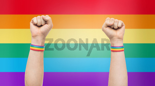 hands with gay pride rainbow wristbands shows fist