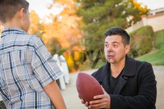 Hispanic Father Holding Football Teaching Young Boy