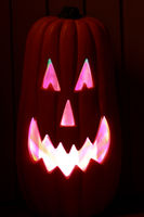 Elongated Jack O Lantern Glowing in Pink and White.