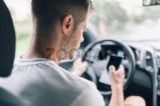 Careless driver using his mobile phone whilst driving a car