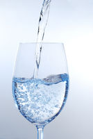 clear transparent water pour into wineglass