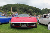 a man looking at a vintage stingray sports car with people looking at vehicles in the park at hebden bridge annual vintage weekend