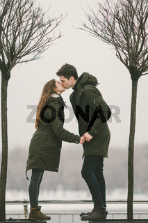 A heterosexual couple young people in love students a man and a Caucasian woman. In winter, in the city square covered with ice, they walk, hug and kiss. Love concept in any weather