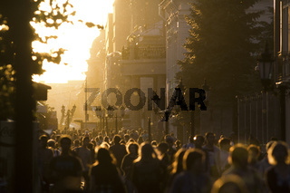 Silhouette crowd of people walking down the street at summer sunset