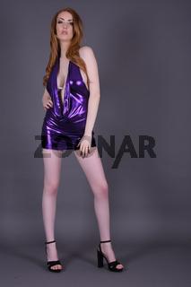 Ashley Foxx, sexy vollbusige Rothaarige, in einem engen lila glanzendem Minikleid