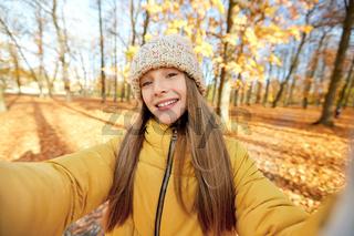 happy girl taking selfie at autumn park