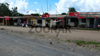 ramshackle village made of recycled materials on the roadside in Tanzania with shops and small homes for local people