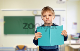 displeased little boy with book at school