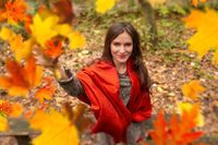 Gorgeous young woman outdoors, in a park autumn scenery, throwing up in the air many yellow leaves, looking at the camera and smiling happy. Body shot, natural light, retouched, vibrant colors
