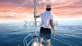 Man standing at the bow of a ship. Yachting, vacation and freedom concept.
