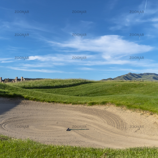 Square Golf course with sand bunker and vibrant fairway under blue sky on a sunny day