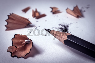 Closeup of black sharp pencil with wooden shaving -Concept of study, learning, write or drawing
