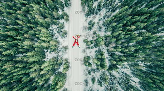 Santa Claus is done after christmas time and makes a snow angel in the snowfall