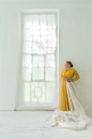 Redhead Woman in Yellow Dress Stands in a White Room