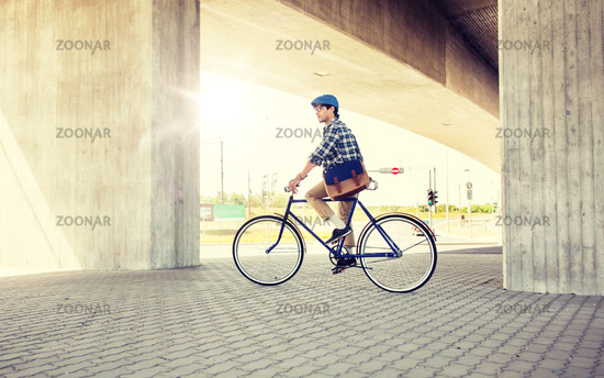 young hipster man with bag riding fixed gear bike