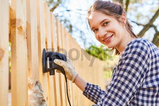 Frau als Handwerker Lehrling beim Zaun abschleifen