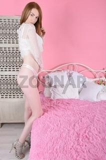 Schlanker, busty Rotschopf in einer Durchsicht vollen Bluse und rosa Unterwasche auf einem bett