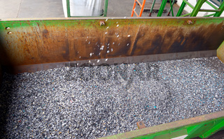 Recycled plastic waste is cut in small pieces and separated in containers, on a recycling plant