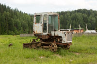 Old tractor on a field in the village in the summer