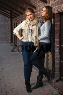 Two young fashion girls in white shirt and dark blue jeans