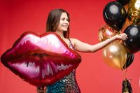 Sexy elegant brunette in beautiful sparkling dress with air balloons.
