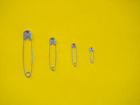 Several safety pins of different sizes. Concept of diversity and inclusion