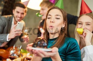 Frau pustet Kuchen aus auf Geburtstagsfeier