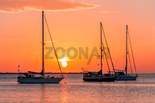 Three sailboats on sea at sunset