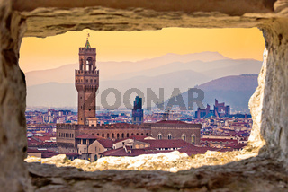 Ancient Florence cityscape and Palazzo Vecchio sunset view through stone window