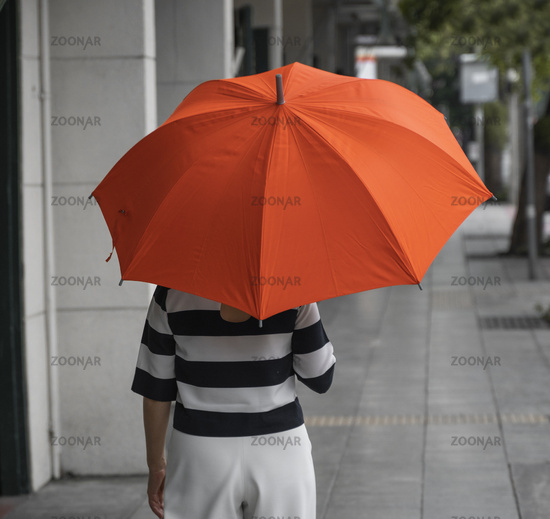 Back view of woman with orange umbrella walking on a street.
