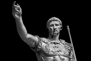 Caesar Augustus, the first emperor of Ancient Rome. Bronze monumental statue in the center of Rome isolated on black background