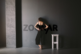 social theme of female loneliness is pain suffering. Abastration of male domestic violence. Young beautiful Caucasian woman in black clothes, strange pose, white chair big dark room. Fear and despair