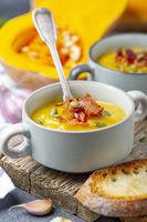 Pumpkin soup with crispy bacon close up.