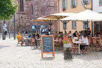 people enjoying drinks in French cafe outside of Saint Thomas' Church in the old city center of Strasbourg
