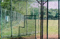 View on empty sports field through net fence