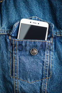 Smartphone in jeans jacket pocket.