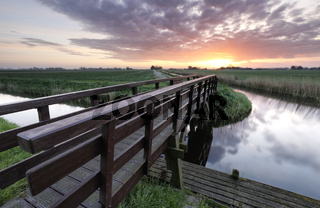 wooden bridge for bicycles via river at sunrise
