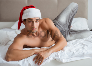 Young sexy man wearing santa hat in bed