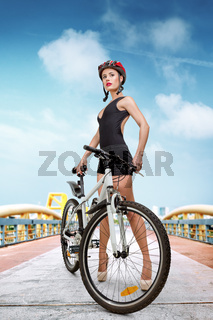 Young sporty woman on city street with bicycle