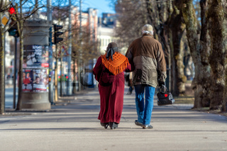 A couple of eldery people in hands are walking through the city street. Rear view.