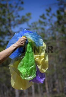 a female hand holds a pile of empty transparent crumpled plastic bags for garbage