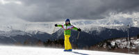 Happy young skier with ski poles in sun mountains and cloudy gray sky before blizzard