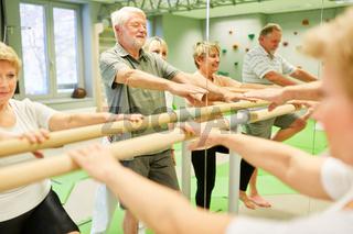 Senioren bei der Krankengymnastik an Ballettstange