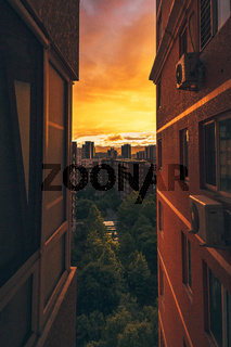 Looking Between Two Apartment Buildings at Cityscape Urban View Sunset Orange Red Afternoon Tight Vertical Space