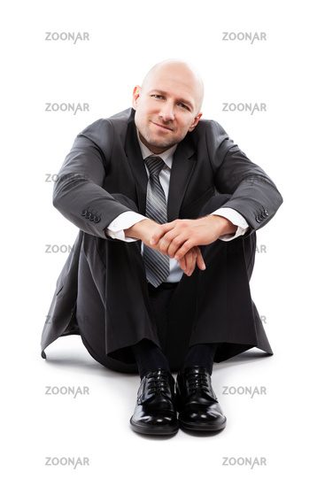 Handsome happy smiling businessman in black suit sitting down floor
