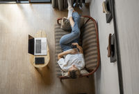 Woman use a smartphone while lying on a sofa with a laptop and ereader on a table. Studying online, freelance. Self employed or freelance girl use a phone and resting from work whith a notebook.