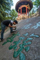 Man painting chinese calligraphy characters on a rock