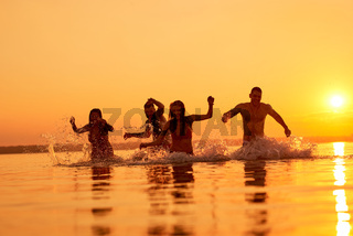 Euphoric friends swimming in evening